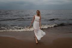 Chodz?ca Pi?kna m?oda blondynki kobiety pla?y boginka w biel sukni blisko morza z falami podczas nied?wi?cznej ponuractwo pogody  zdjęcie stock