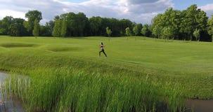 Chodzenie przedni widok sport kobieta jogging wzdłuż łąki blisko rzeki zbiory wideo