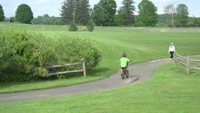 Chodzić i jechać na rowerze na ścieżce w parku zbiory wideo