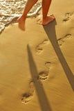 Chodzi wzdłuż plaży, odciski stopy w złotym piasku zdjęcie stock