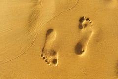 Chodzi wzdłuż plaży, odciski stopy w złotym piasku obrazy stock