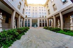 Chodzi z kwadratowymi kolumnami i statuami wśród nowożytnych budynków budynków w Mediolan, Włochy Fotografia Royalty Free