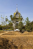 Choeung Ek memorial with mass graves in the foreground. In the foreground- mass graves where thousands of bodies were burried following the horrors of the Khmer Royalty Free Stock Images