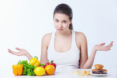 Choice. Doubting the girl with a healthy diet and sweet on a white background royalty free stock photography