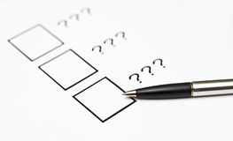 Choice. Three check boxes without labels, question marks instead, a pen. Shallow depth of field Royalty Free Stock Photo