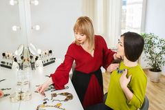 Choice of accessories. Portrait of beautiful young women choosing fashion jewelry. Choice of accessories with a stylist Stock Photography