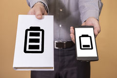 Choice between book and cellphone battery life. Man offering a choice between a book and a smartphone. Battery life concept Royalty Free Stock Images