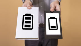 Choice between book and tablet battery life. Man offering a choice between a book and a tablet. Battery life concept Royalty Free Stock Image