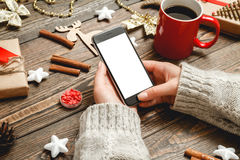 The choice of Christmas gifts in interenete concept. Girl in a cozy knitted sweater uses the phone while sitting at a table with Christmas accessories Royalty Free Stock Photo