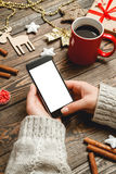 The choice of Christmas gifts in interenete concept. Girl in a cozy knitted sweater uses the phone while sitting at a table with Christmas accessories Stock Image