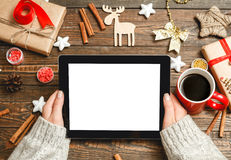 The choice of Christmas gifts in interenete concept. Girl in a cozy knitted sweater uses a tablet, sitting at a table with Christmas accessories Stock Images