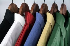 Choice of colorful shirts. Man's wear: choice of colorful shirts on wooden hangers royalty free stock photography