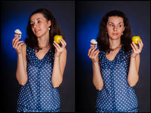 Diet choise. Young woman making a choice between a healthy apple or delicious cupcake royalty free stock photography