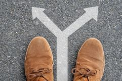 Shoes in front of an arrow indicating opposite directions stock illustration
