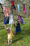 Choice of dresses. Little girl standing before the tree with dresses hanging on branches Royalty Free Stock Photo
