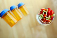 Choice between druds, pills and vegetables royalty free stock image