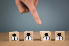 Choice of an employee leader from the crowd. the hand points to the wooden cube that symbolizes that the hand makes the choice stock images