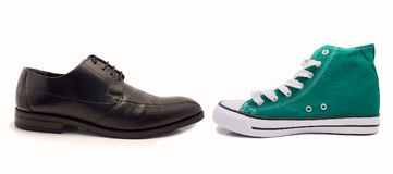 Formal or casual. Choice between formal shoe and sneaker by profile over white background stock image