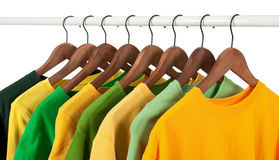 Choice of green and yellow casual shirts. Choice of green and yellow shirts and t-shirts on wooden hangers, isolated on white Royalty Free Stock Photo