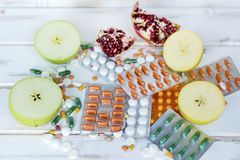 Choice Between Healthy Fruits or Pills. Choice Between Healthy Nutrition or Medical Supplements.Healthy Life Concept on a white wooden background Royalty Free Stock Photography