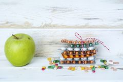 Choice Between Healthy Fruits or Pills. Choice Between Healthy Nutrition or Medical Supplements.Healthy Life Concept on a white wooden background Stock Photography