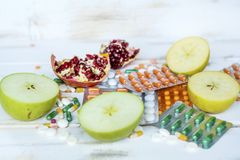 Choice Between Healthy Fruits or Pills. Choice Between Healthy Nutrition or Medical Supplements.Healthy Life Concept on a white wooden background Stock Photo