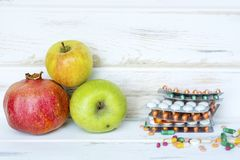 Choice Between Healthy Fruits or Pills. Choice Between Healthy Nutrition or Medical Supplements.Healthy Life Concept on a white wooden background Royalty Free Stock Images