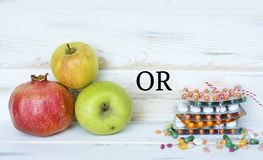 Choice Between Healthy Fruits or Pills. Choice Between Healthy Nutrition or Medical Supplements.Healthy Life Concept on a white wooden background Royalty Free Stock Photo
