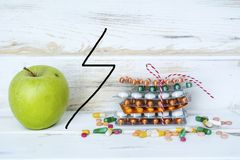 Choice Between Healthy Fruits or Pills. Choice Between Healthy Nutrition or Medical Supplements.Healthy Life Concept on a white wooden background Stock Image