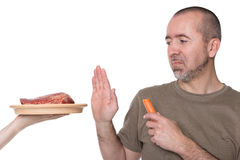 Choice between meat and vegetables. Man rejects offered meat on a plate Stock Photos