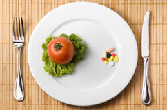 Choice of medicine. Drugs on the plate illustrating choice between medicine and healthy eating Royalty Free Stock Photo