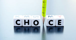 The choice mut be green. Text ' choice ' in black uppercase letters on white cubes with a green pencil replacing letter ' i ' , on reflecting surface Stock Images