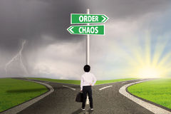 Choice of order or chaos. Little businessman standing on the road looking at signpost of order and chaos Stock Image