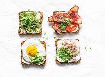 Choice of sandwiches for breakfast, snack, appetizers - avocado puree, fried egg, tomatoes, bacon, cream cheese, smoked mackerel g stock image