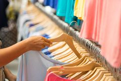 Choice shirts in boutique. Buyer chooses a T-shirt in a modern boutique Royalty Free Stock Photo