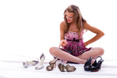 The choice of shoes is very difficultly. Isolated on white Royalty Free Stock Images