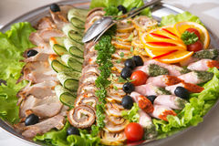 Choice of snacks. Dish with set of snack of ham, rolls, paste and vegetables Stock Photography