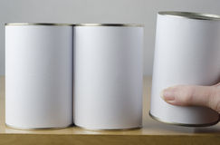 Choice of Three Tin Cans. Conceptual image of three tin cans with blank white paper labels on a shelf, with middle aged female hand reaching in from right of Stock Photo