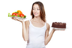 Choice between vegetables and chocolate cake Stock Photo