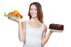 Choice between vegetables and chocolate cake Stock Image