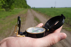 Choice of a way. Photo of a compass in a hand on a background of road Royalty Free Stock Images