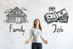 Choice between work and family. Meditating young european woman on concrete background with house and money sketch. Choice between work and family Stock Photography