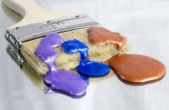 Choices. Paintbrush with three choices of metallic paint colors including purple, blue and copper Royalty Free Stock Photo