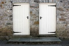 Choices. Two white old wooden doors with black ironmongery and steps set into an old stone wall Royalty Free Stock Photography