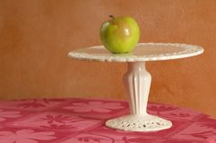 Choices. Green apple blushed with pink on a cake pedestal plate Royalty Free Stock Images