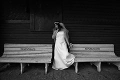 Choices. Bride standing between two benches.  One reads Democrats the other Republicans Stock Images