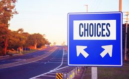 Choices decision. Road sign on a highway with two different choices of path and arrows left and right indicating the destination Stock Image