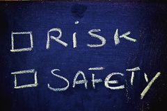 Choices: risk vs. safety. Chalk writings on blackboard, choice between risk and safety Stock Images