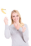Choices: Woman Throws Away Healthy Banana For Cookie Royalty Free Stock Photography
