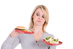 Choices: Woman Trying To Choose Between Burger and Healthy Wrap Stock Photos